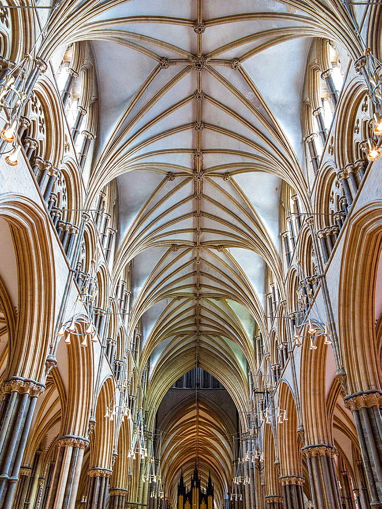 Interior of Lincoln Cathedral showing knave and decorated ceiling.