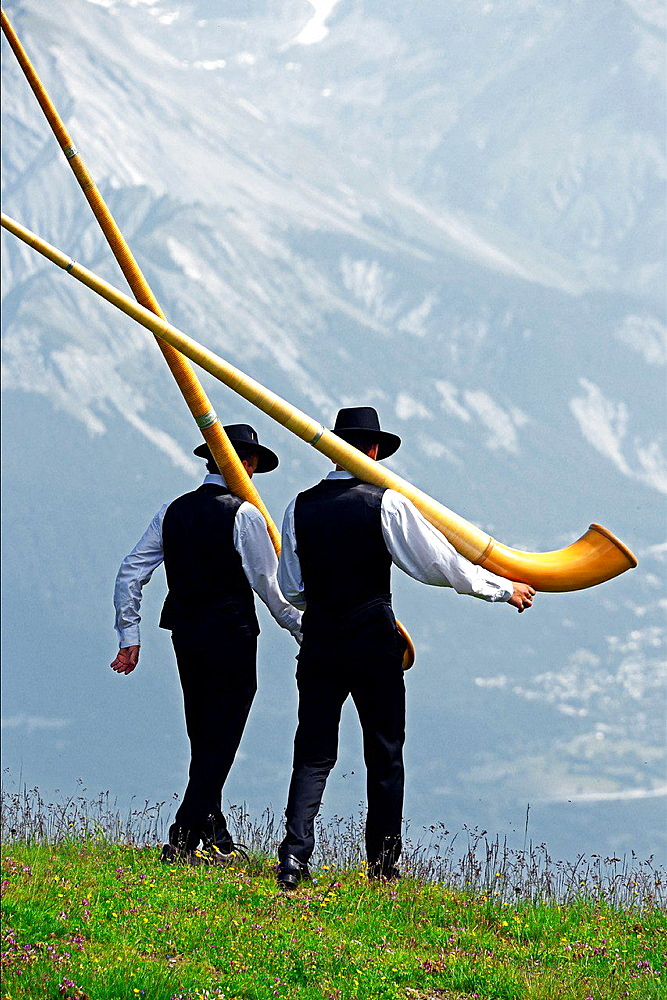Two men walking with alphorns, Swiss Alps, Nendaz, canton Valais, canton Wallis, Switzerland