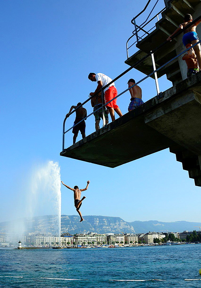 boy jumping from diving tower to waters of Geneva Lake, famous fountain on the lake, Jet d'Eau in the background, Geneva, Switzerland