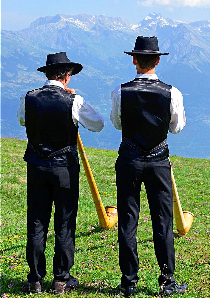 Two alphorn playres in Swiss Alps, International Alphorn Festival, 27-29 July 2013, Nendaz, canton Valais, canton Wallis, Switzerland.