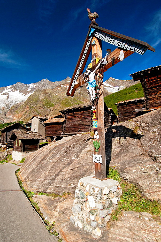 Saas Fee, old traditional Swiss buildings and traditional cross, street scene, canton Valais, canton Wallis, Switzerland