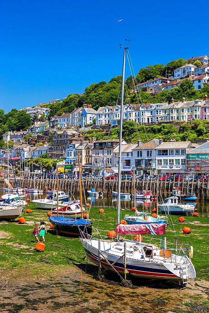 Fishing boats and sailing yachts moored in Looe harbour during low tide, Cornwall, England, United Kingdom, Europe.