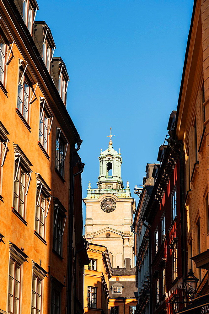 Tower from Church of St. Nicholas, Storkyrkan, Stockholm Cathedral rises between buildings, Gamla Stan, old town, Stockholm, Sweden.