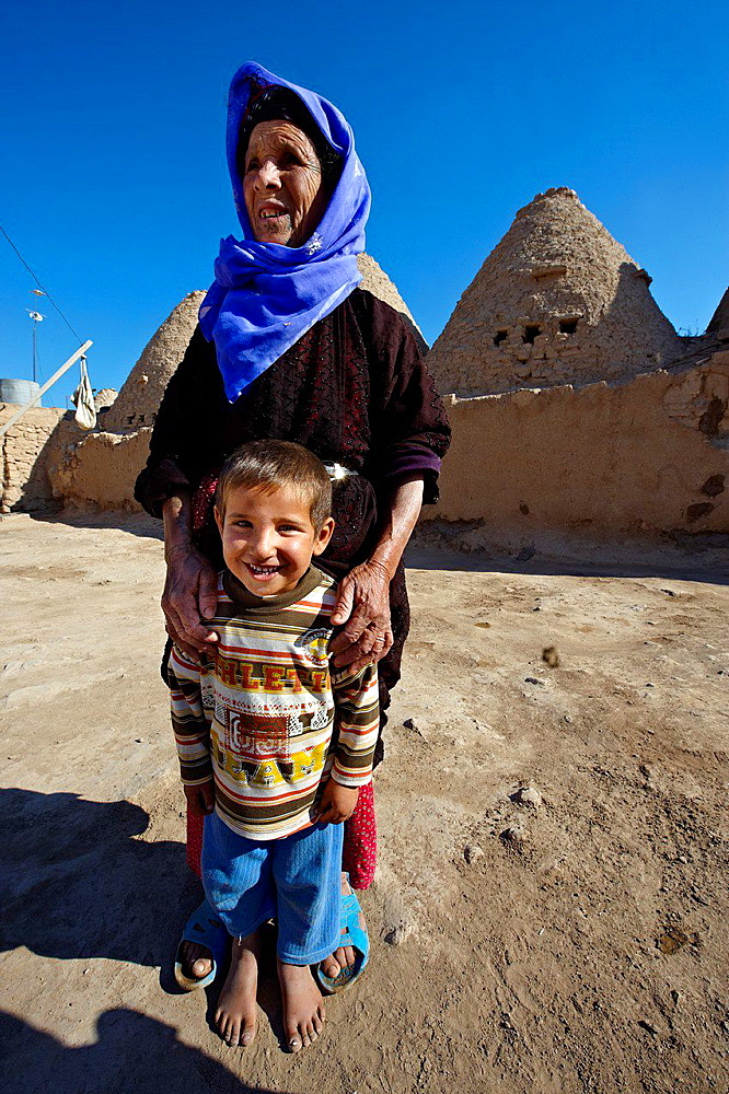 Grandmother and child standing outside an adobe beehive house in Harran, Southern Anatolia, Turkey