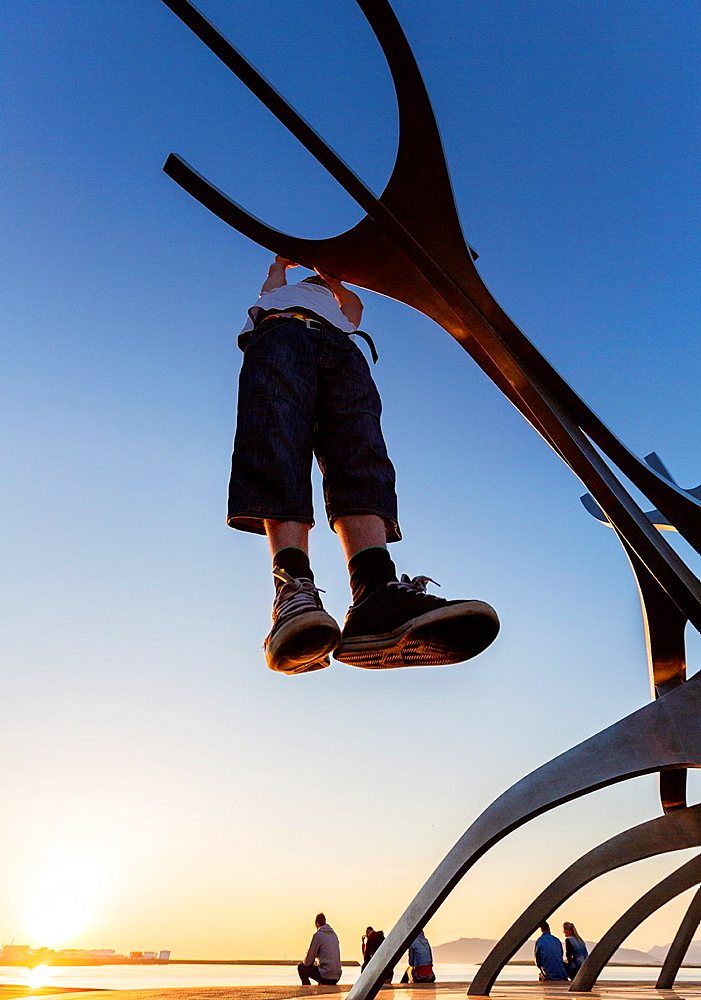 Teenager hanging on metal sculpture known as The Solfar, Reykjavik, Iceland.