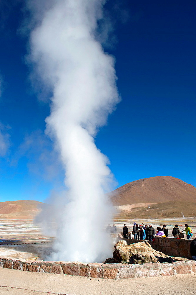 Tourists at hot springs at El Tatio Geysers geothermic basin near San Pedro de Atacama in the Atacama Desert, northern Chile.