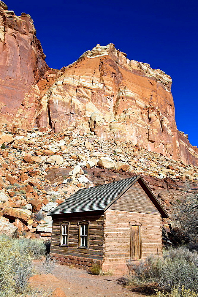 One-room Frutia Schoolhouse with colorful sandstone rock formations, Historic Fruita, Capitol Reef National Park, Utah, United States of America.