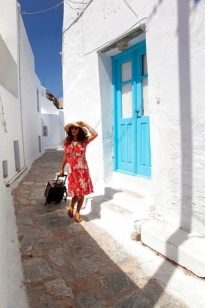 Tourist woman walking through the alley, Amorgos, Cyclades Islands, Greek Islands, Greece, Europe.