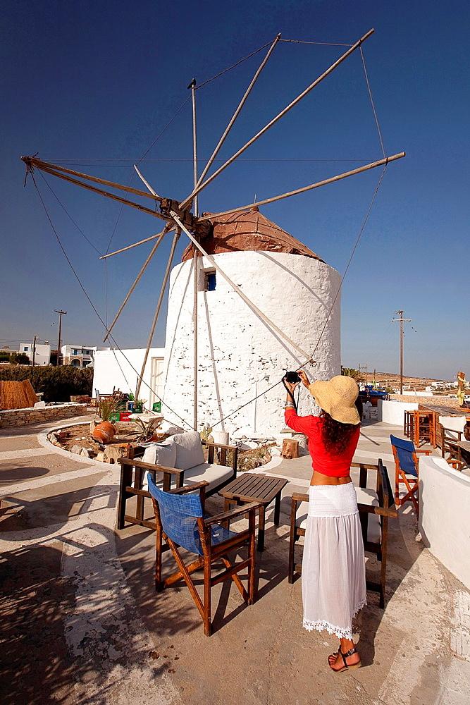 Tourist woman taking a photo of the windmill, Koufonissi, Cyclades Islands, Greek Islands, Greece, Europe.