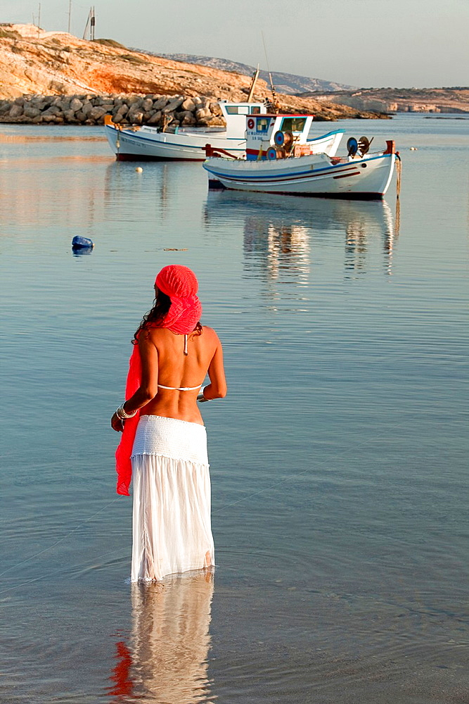 Woman with a scarf in the sea, Koufonissi, Cyclades Islands, Greek Islands, Greece, Europe.