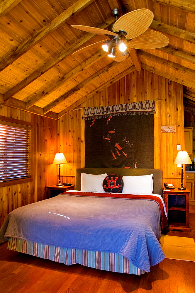 Guest bed in rustic luxury in cedar wood cabin, El Capitan Canyon Resort, near Santa Barbara, California.