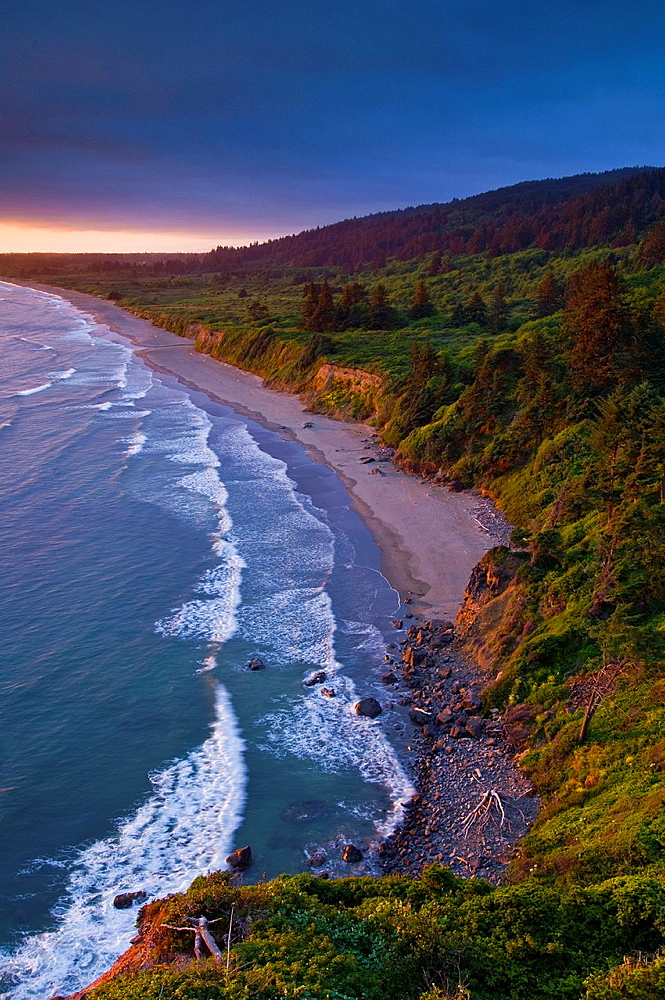 Sunset light and clouds over the hills above Enderts Beach, near Crescent City, Redwood National Park, California.
