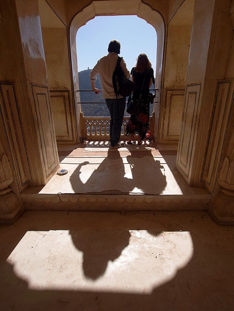 Couple enjoying view from the balcony of historic structure in Jaipur, Rajasthan, India.