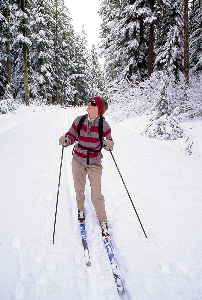 USA, Oregon, Willamette National Forest, Woman skiing below Breitenbush Lake