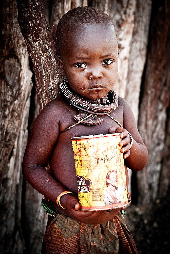 Himba girl with can looking at the camera in a village near Epupa Falls, Kunene, Namibia, Africa.