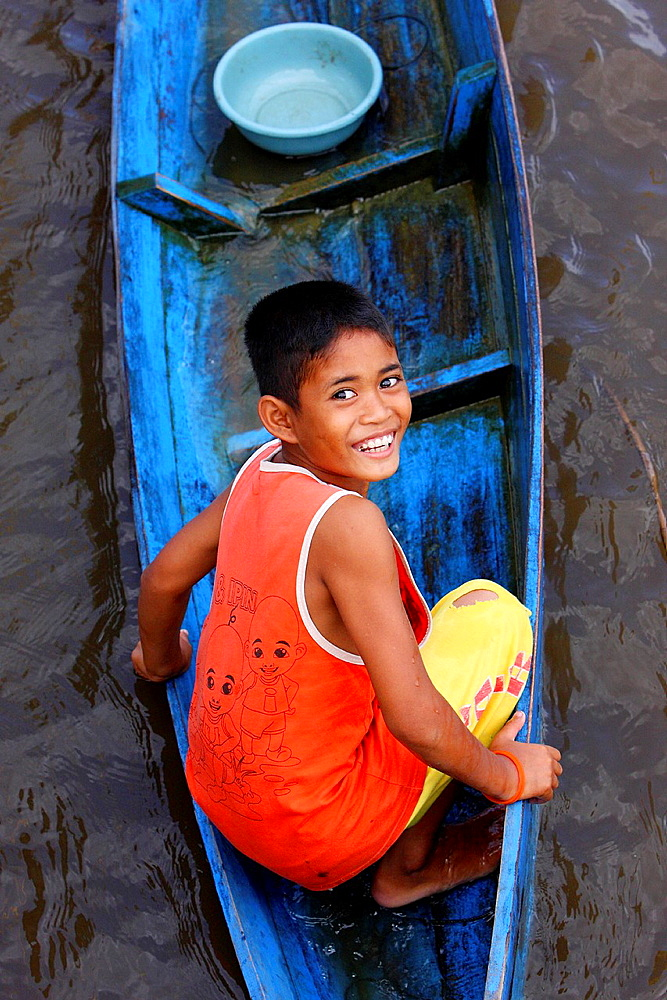 Close up of a Young boy cruising in his canoe through, kalimantan, borneo.