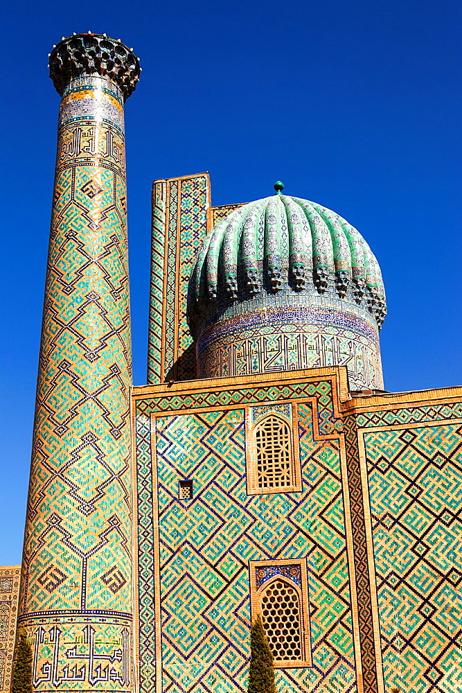 A minaret and dome of Sher Dor Madrasah, also known as Shir Dor Madrasah, Registan Square, Samarkand, Uzbekistan.