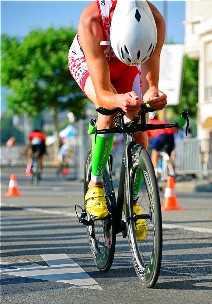 single female athlete cycling, bicycle race, 25th International Geneva Triathlon, on July 21, 2013, Quai Wilson, Geneva, Switzerland.