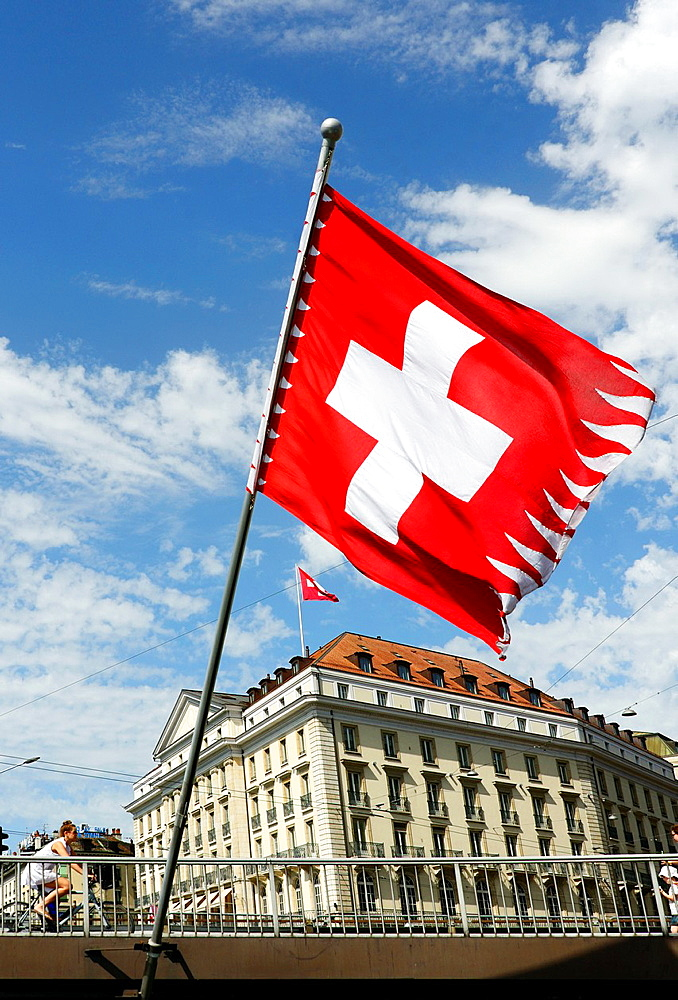 Swiss flag on Mont Blanc bridge, Geneva, Switzerland, Four Seasons Hotel des Bergues Geneva in the background