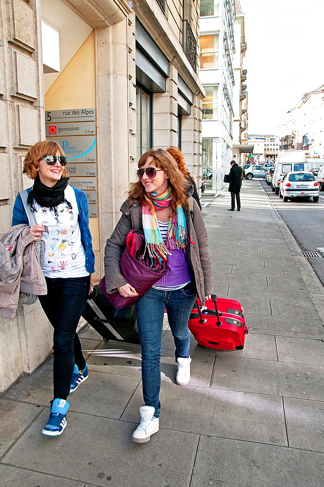smiling young women - travelers pulling suitcases, street near main train station, Geneva, Switzerland