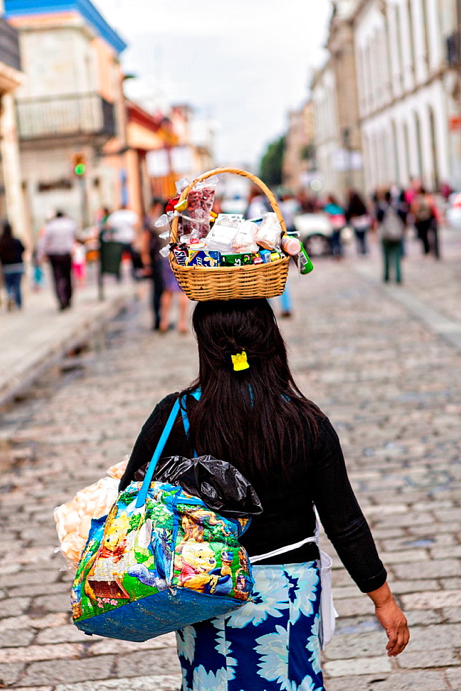 A Mexican street vendor walks down the Alcala pedestrian mall with her goods balanced on her head in Oaxaca, Mexico.
