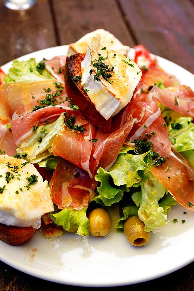 Salad with Goat Cheese and Prosciutto on Chavonnes lakeside restaurant. Villars, Vaud, Switzerland, Europe.