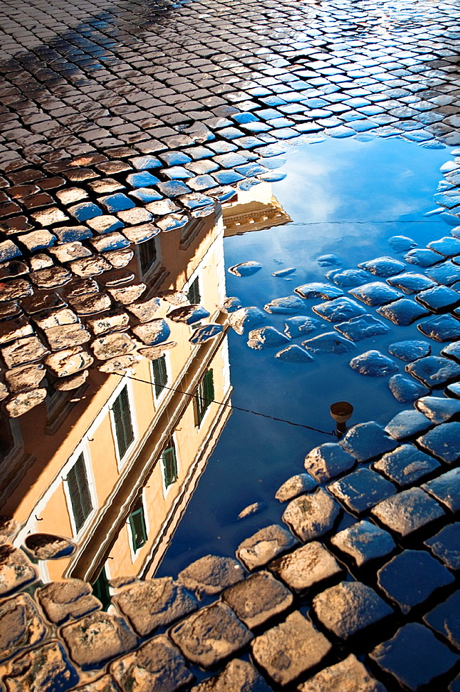 Reflection of house in rain puddle on cobbled street in Trastevere, Rome, Italy.