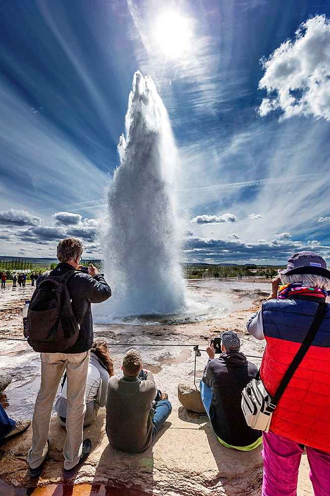 Tourist taking pictures of Strokkur Gesyer erupting, Iceland.