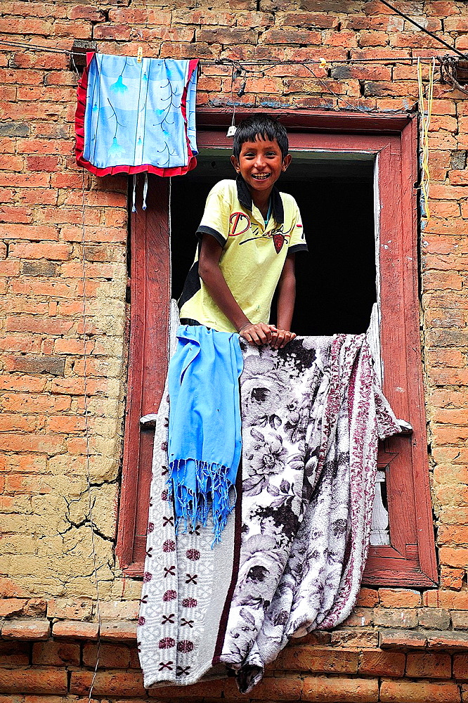 Child looking at a window, Panauti, valley of Kathmandu, Nepal
