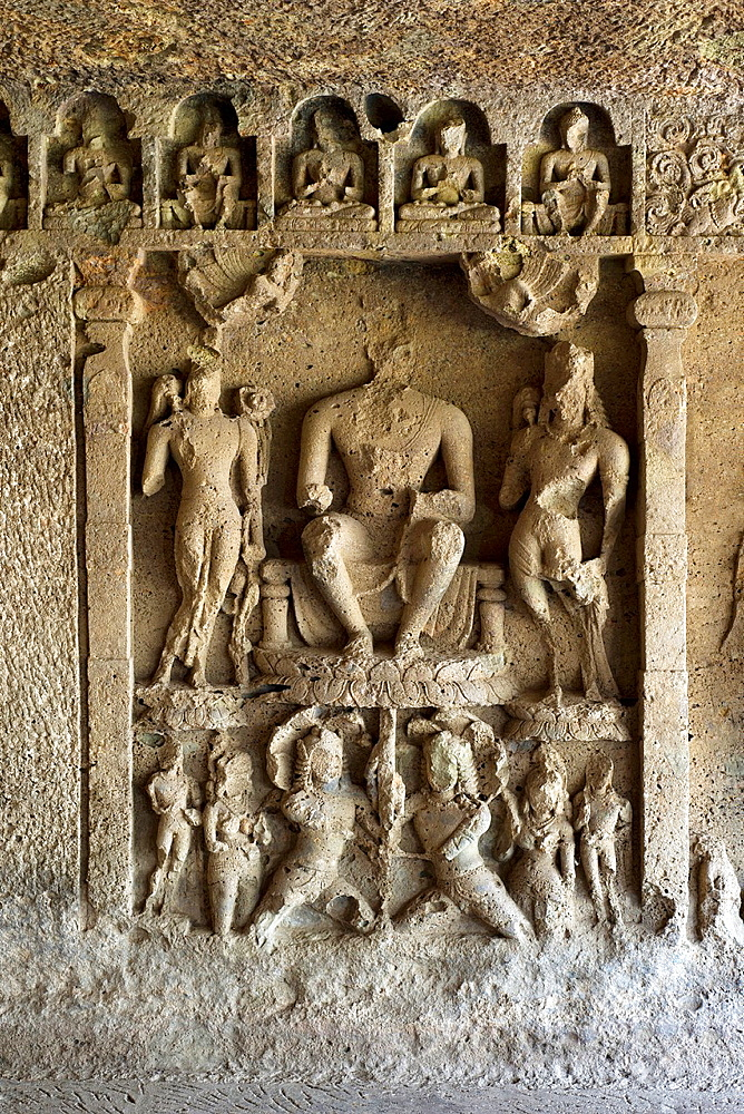 Kondivite rock-cut caves, Mumbai. Chaitya No.9, Buddha panel- Buddha seated in Pralambapadasana with his feet on the Lotus, the Nagas holding the Lotus stalk. And miniature Buddha figures at the top.