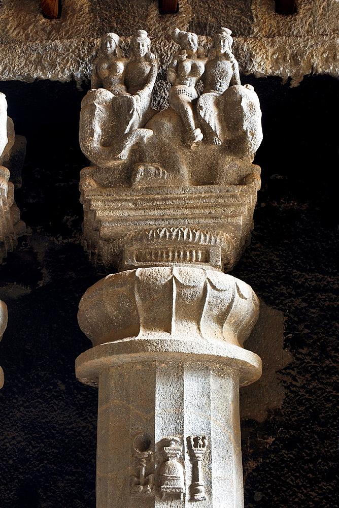 Pillar details showing votive stupa, miniature lion pillar on pillar shaft and elephant riders. Karla Caves, Pune, Maharashtra India.
