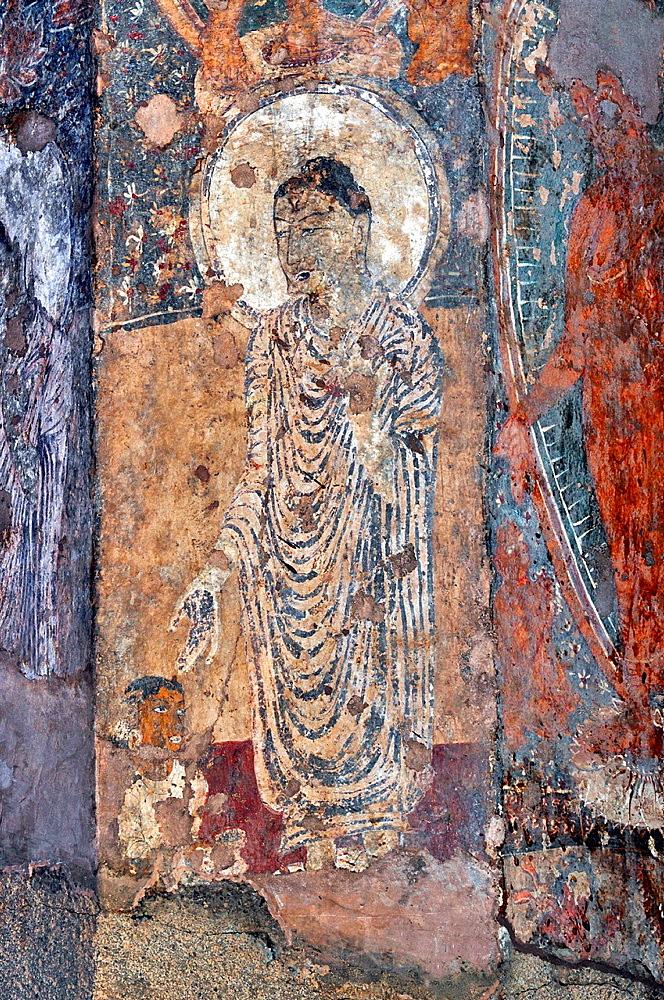 Cave 10 : Painting. Standing Buddha image in white robe with a devotee seated. Ajanta Caves, Aurangabad, Maharashtra, India.