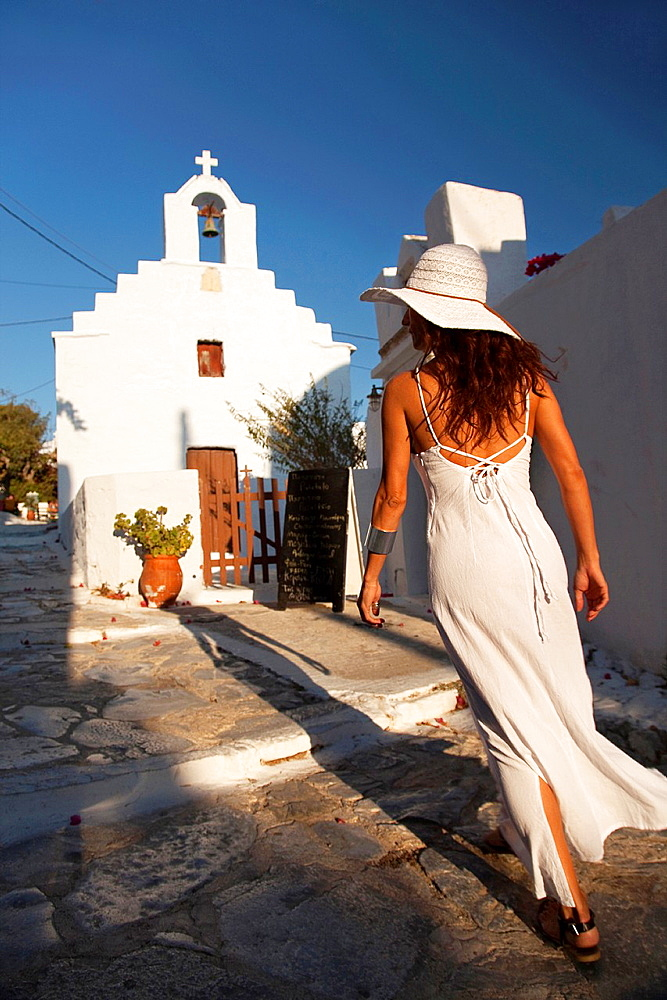 Woman walking towards a chapel, Amorgos, Cyclades Islands, Greek Islands, Greece, Europe.