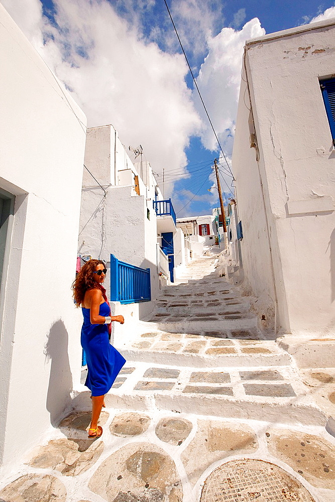 Woman walking in the alleys of the town, Mykonos, Cyclades Islands, Greek Islands, Greece, Europe.
