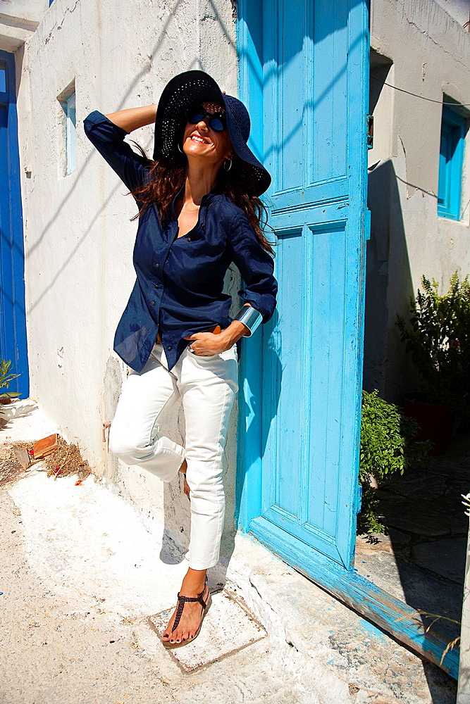 Woman at the entrance of a house door, Amorgos, Cyclades Islands, Greek Islands, Greece, Europe.