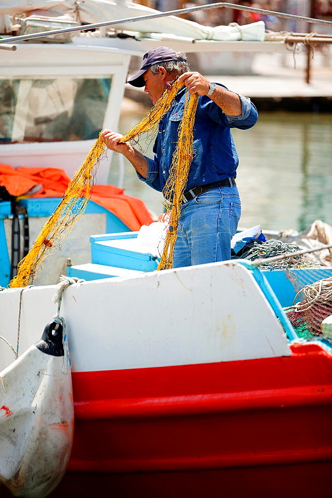 Greek fisherman pulling his net at the port, Mykonos, Cyclades Islands, Greece, Europe.