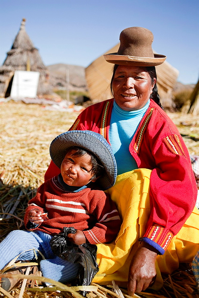Aymara indigenous woman with her grandson Uros Islands, Lake Titicaca, Puno, Peru, South America.