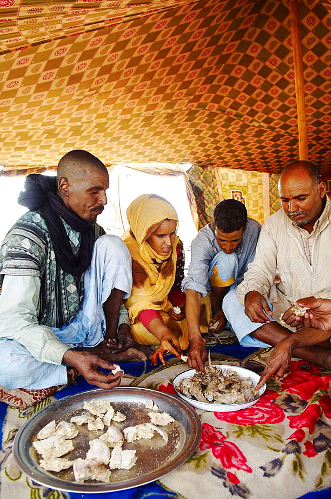 Nomad family eating goat and traditional bread cooked under sand, Chinguetti, Adrar Plateau, Sahara Desert, Mauritania - 817-88538