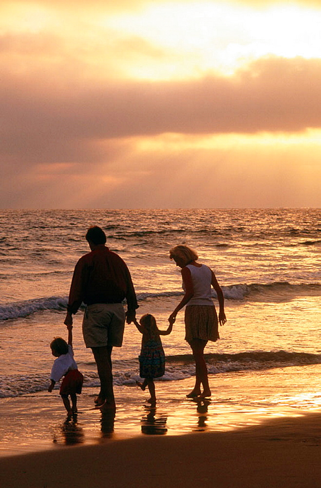 Family enjoying sunset at the beach