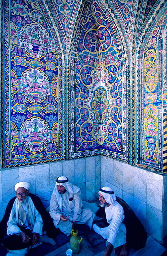 Men sat in the Sanctuary Mosque Al Kadhimain, Baghdad, Iraq