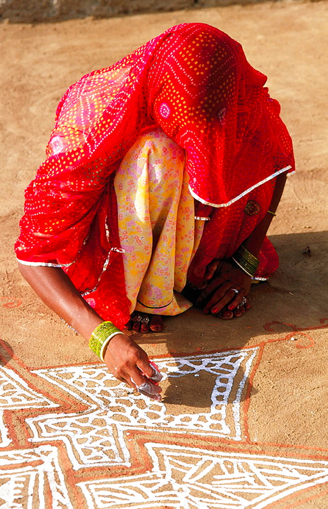 Indian woman painting a mandana in Rajasthan, India