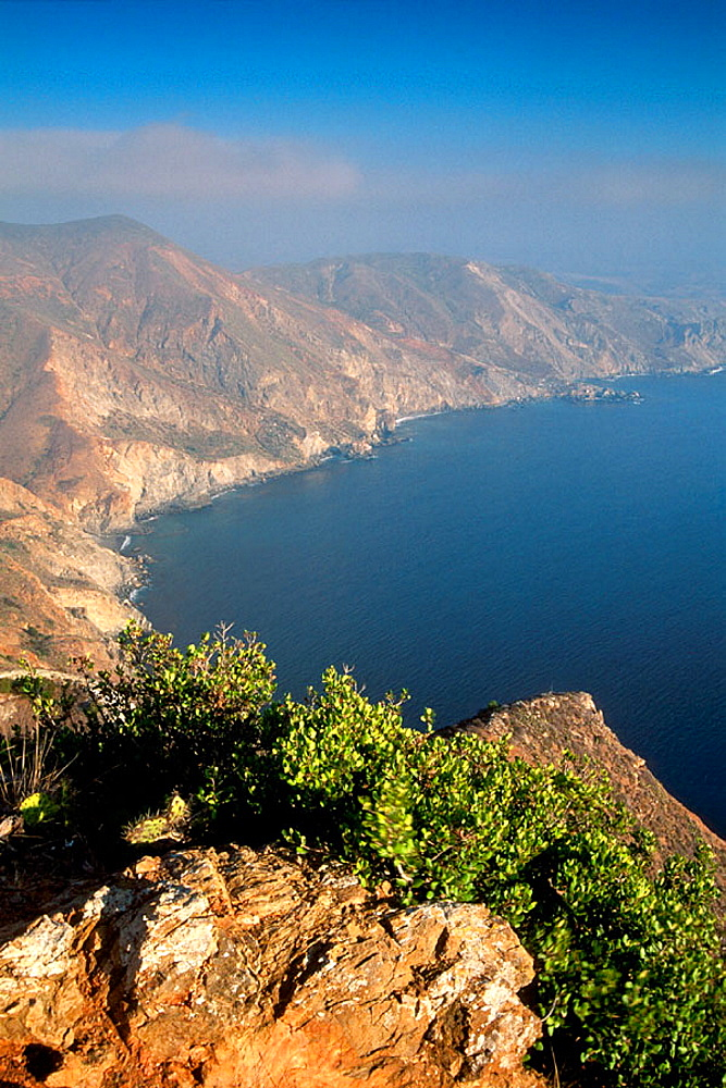 Steep rugged hills, coastal cliffs, and blue Pacific Ocean water, near Two Harbors, Catalina Island, California, USA