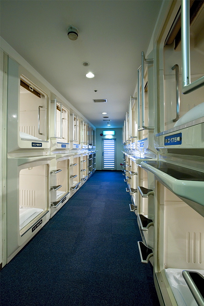 Rows and stacks of sleeping compartments along one corridor at a capsule hotel in Osaka, Japan, Asia