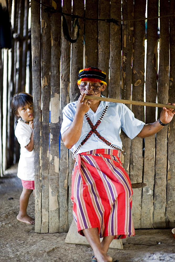 An Achuar man plays an Achuar flute, Amazon, Ecuador, South America - 824-105