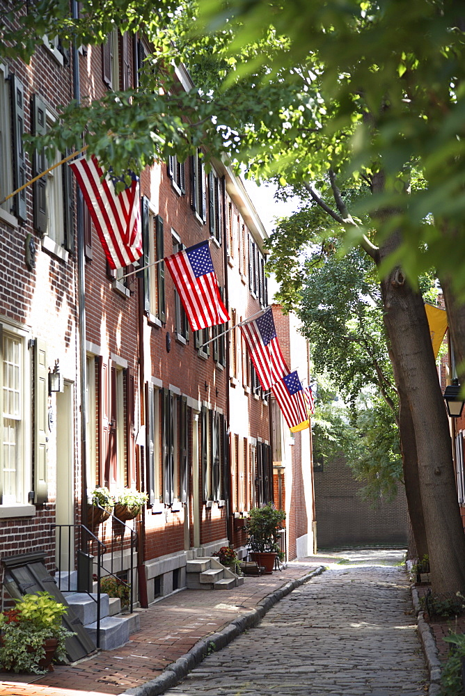 Flags displayed on homes on cobblestone American Street, in the Society Hill neighborhood of Philadelphia, Pennsylvania, United States of America, North America - 825-113