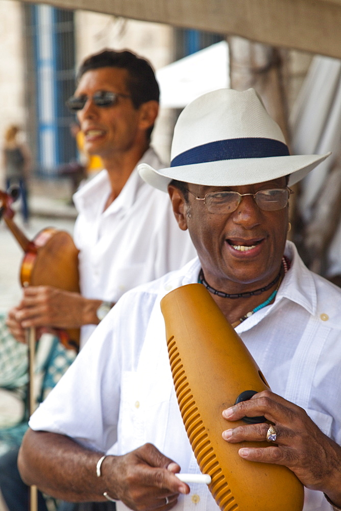 Men playing music on a guiro, a percussive instrument essential in salsa music, and a violin, in Plaza de la Catedral, Havana, Cuba, West Indies, Central America