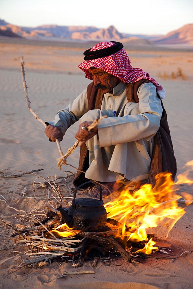 Bedouin making tea on open fire in the desert of Wadi Rum, Jordan, Middle East