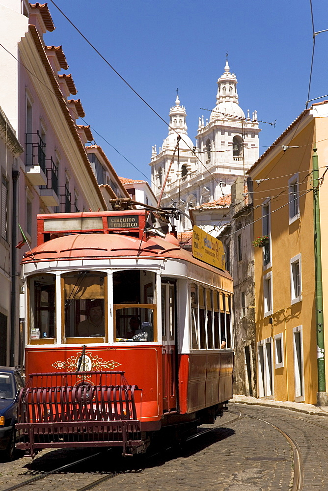 A tram runs along the tourist friendly Number 28 route in Alfama, Lisbon, Portugal, Europe