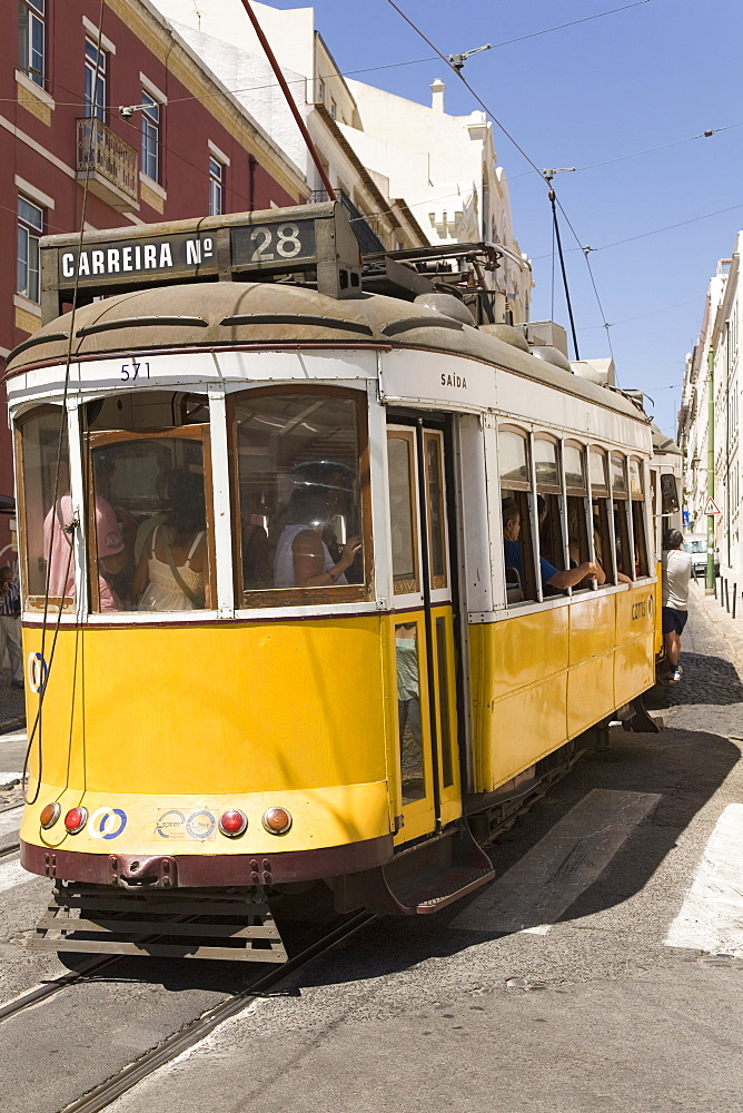 A number 28 tram runs along the scenic route popular with tourists in the Alfama district of Lisbon, Portugal, Europe