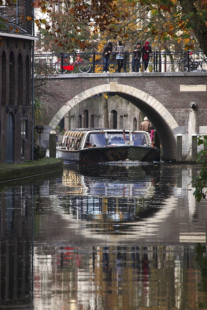 A sightseeing barge under a bridge on the Oudegracht Canal in the Dutch city of Utrecht, Utrecht Province, Netherlands, Europe